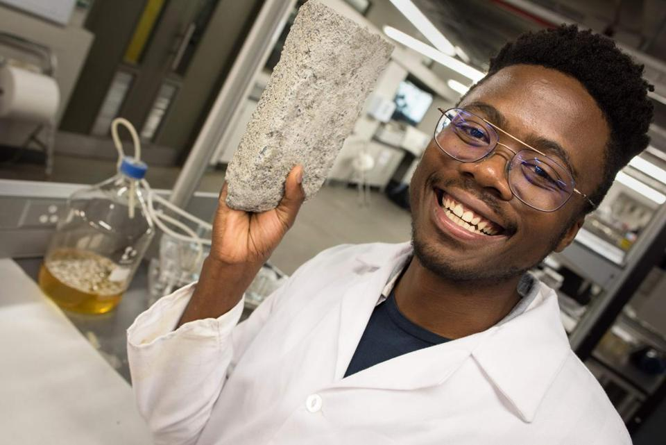 Vukheta Mukhari, one of the developers of the world's first bio-brick which uses human urine as one of the binding components, show off one of their bricks in the lab at the Department of Civil Engineering at the University of Cape Town (UCT) on November 2, 2018 in Cape Town. (Photo by Rodger BOSCH / AFP)RODGER BOSCH/AFP/Getty Images