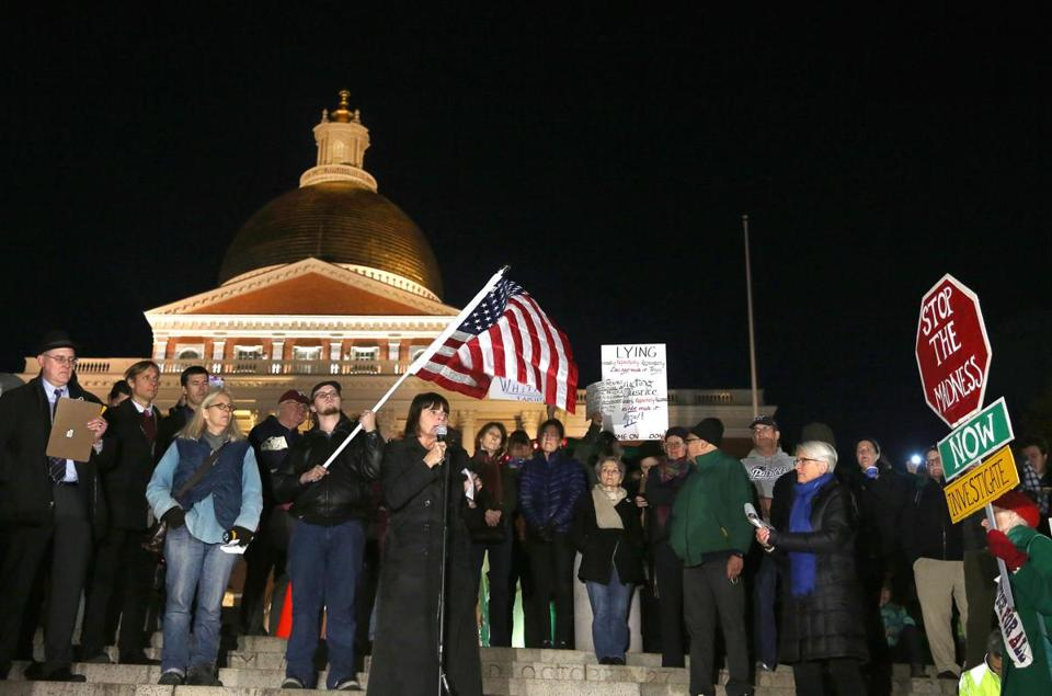 Middlesex District Attorney Marian Ryan (cq) is one of the speakers. (Suffolk University student Scott Damon (cq), 21, holds the flag behind her.) People hold a protest to protect the Mueller investigation, on Boston Common, across from the State House.