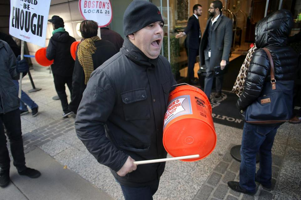 Boston, MA - 11/08/18 - Valter Mucaj (cq) bangs a plastic bucket and shouts union slogans in front of the Ritz as patrons exit the lobby. Banging on makeshift drums and shouting slogans, UNITE HERE Local 26 hotel workers are on strike at seven Marriott hotels in Boston, including in front of the Ritz Carlton. Residents of the swanky Millennium Place condos are used to putting on the ritz, but for the last six weeks they've been putting up with The Ritz: A cacophonous, 12-hour-a-day racket led by striking Marriott workers. Now, three condo associations from buildings nearby (but not associated with the labor dispute) are suing the city to get police to enforce noise ordinances in the first class action permit case in recorded history. (Lane Turner/Globe Staff) Reporter: (ramos) Topic: (09nestorritz)