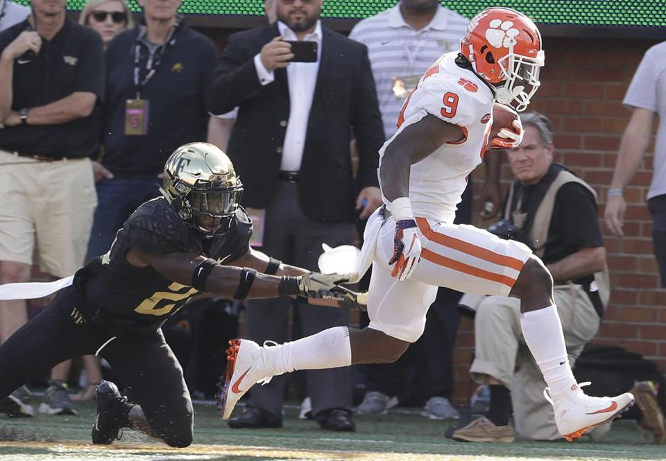 Clemson's Travis Etienne (9) is knocked out of bounds by Wake Forest's Essang Bassey (21) during the first half of an NCAA college football game in Charlotte, N.C., Saturday, Oct. 6, 2018. (AP Photo/Chuck Burton)