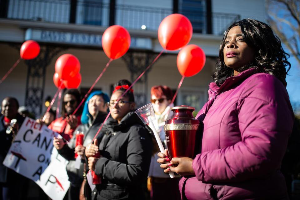 Sophia Bishop-Rice held the ashes of her uncle, Roger C. Herbert, and was joined by other mourners outside Davis Funeral Home in Roxbury on Sunday.