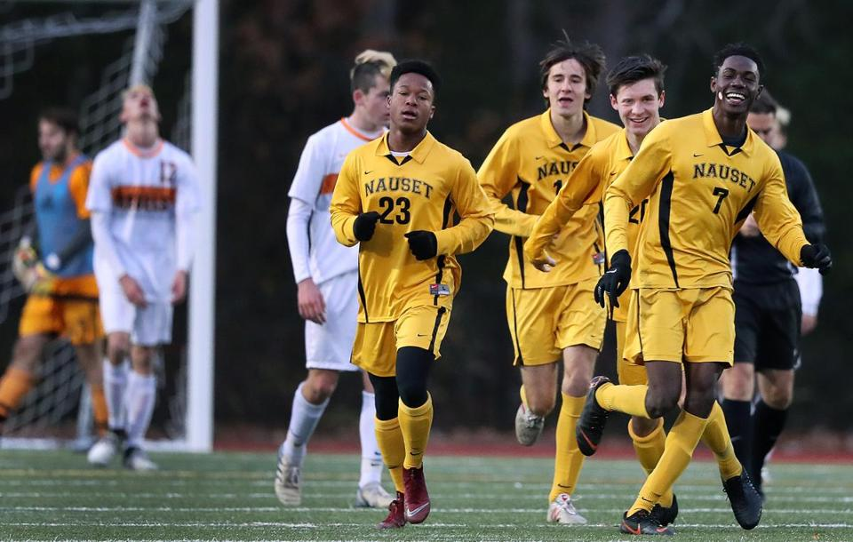 Canton, MA: 11-12-18: Nauset's Romell Brown (7, right) is all smiles after teammate Shavar Champagnie (23) scored in the second half to give Nauets a 2-0 lead, on their way to a 2-1 victory. Walpole players are not as happy in backround at far left. Nauset took on Walpole in the Boy's Soccer Division Two South Championship game at Canton High School. (Jim Davis/Globe Staff)