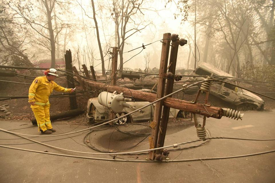 CalFire firefighter Scott Wit surveyed burnt out vehicles near a fallen power line on the side of the road after the Camp fire tore through the area in Paradise, Calif.