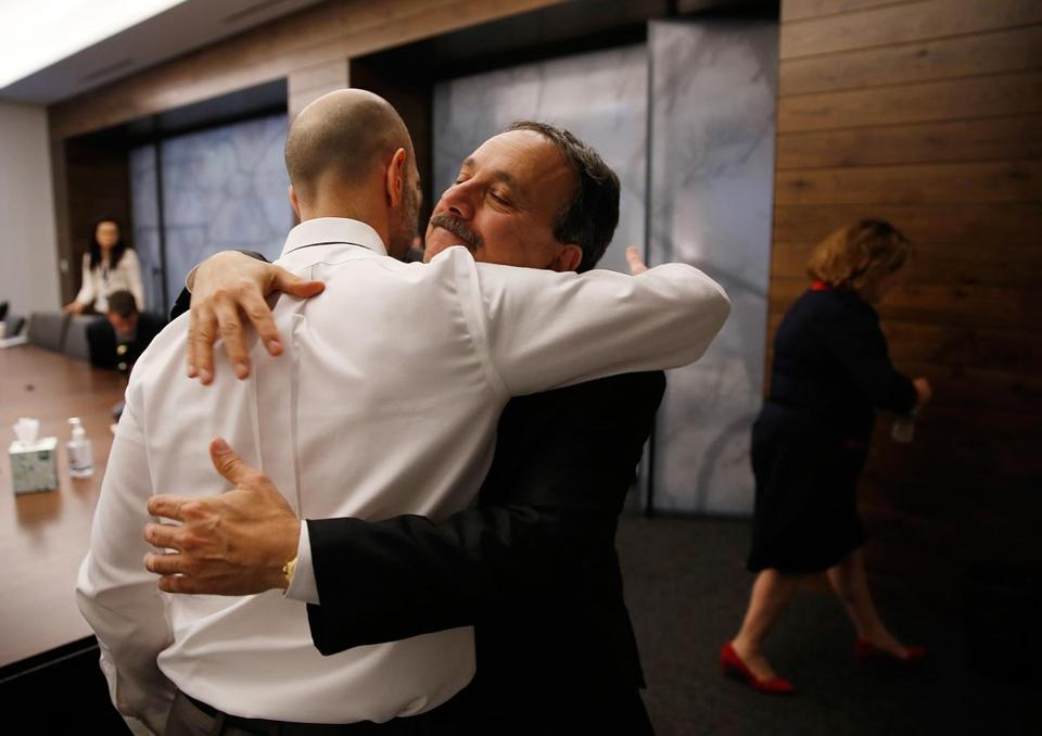 Peter DeMarco (left) and Dr. Assaad Sayah, chief medical officer for Cambridge Health Alliance, embraced Tuesday.