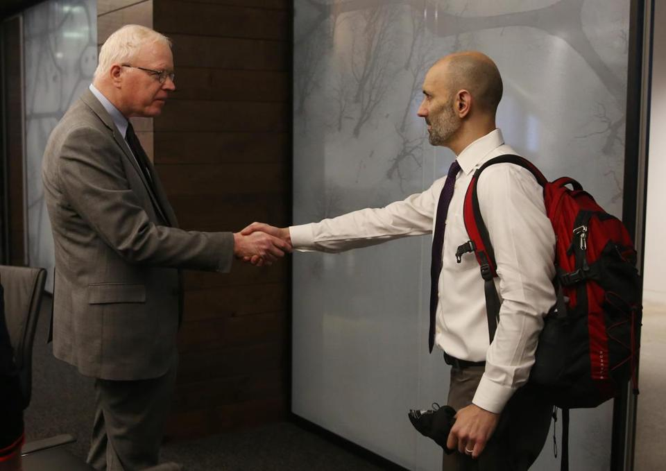 Boston, MA, 11/13/2018 -- Patrick Wardell, chief executive officer (L) shakes hands with Pete DeMarco at the start of a meeting where he and other executives answered questions about the death of DeMarco's wife, Laura Levis. (Jessica Rinaldi/Globe Staff) Topic: 14somerville Reporter: