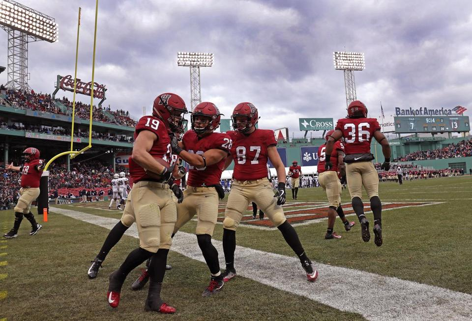 With Fenway Park as backdrop Harvard Crimson wide receiver Tyler Adams (19) celebrates with his teammates after his touchdown during the second quarter gave the Crimson a 13-7 lead over Yale.