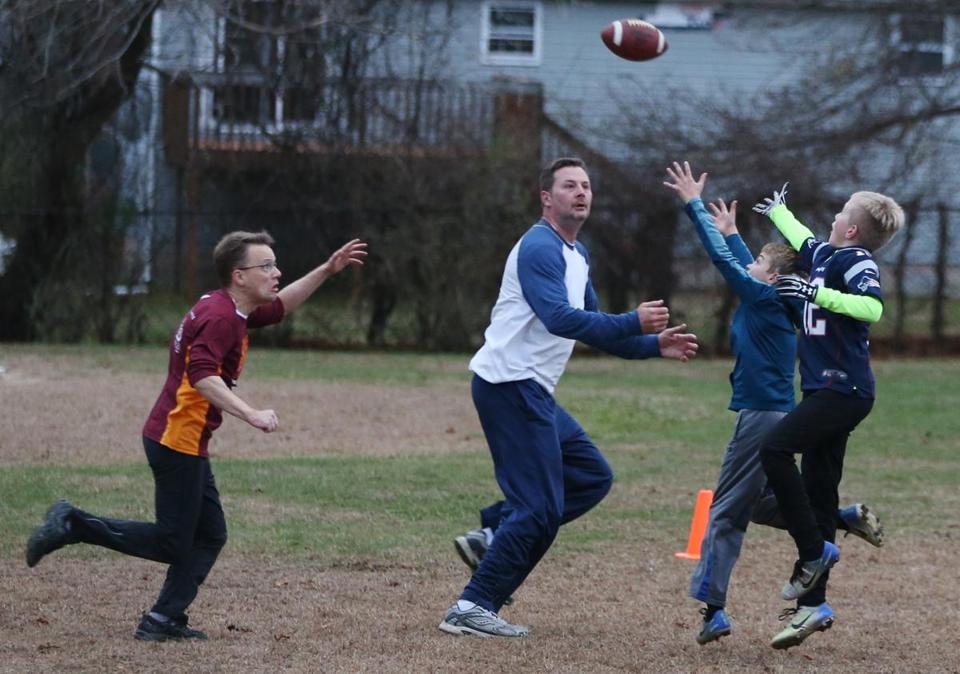 Mystic, CT - 11/18/2018- ] William Korinek, CEO of Astrocyte Pharmaceuticals, plays tag football at ST Butler Elementary School in Mystic with his two sons and longtime friends on Sunday, November 19, 2018. Korinek and Astrocyte Pharmaceuticals are now developing a drug to treat concussions. (Michael Swensen for The Boston Globe) Topic: (business)