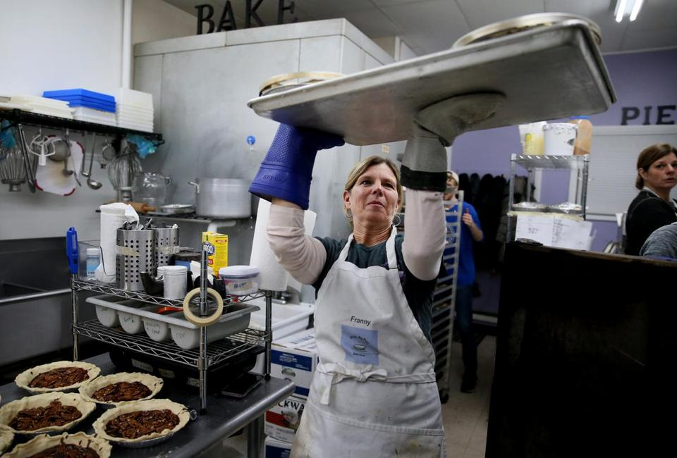 Fran Kolenik carried a tray of apple pies to the oven at her Drive-By Pies in Brookline. She's baking 550 pies by Thanksgiving eve.