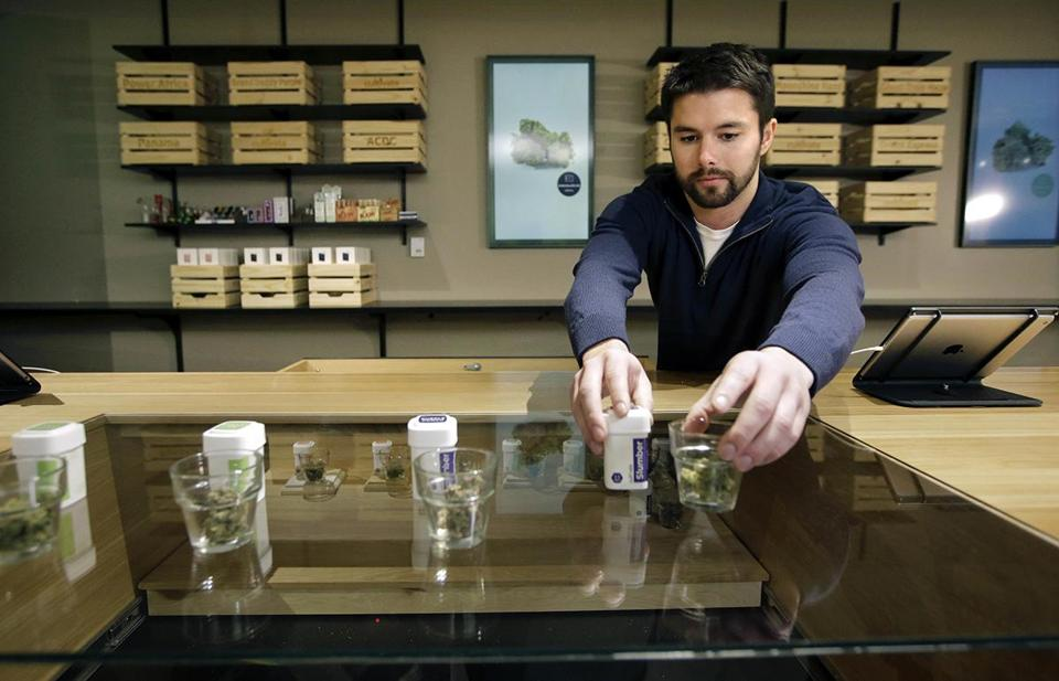 LEGAL POT SLIDER Sam Barber, president and CEO of the Cultivate dispensary, arranges smokable strains of cannabis before opening on the first day of legal recreational marijuana sales, Tuesday, Nov. 20, 2018, in Leicester, Mass. Cultivate is one of the first two shops permitted to sell recreational marijuana in the eastern United States, more than two years after Massachusetts voters approved it in 2016. (AP Photo/Steven Senne)