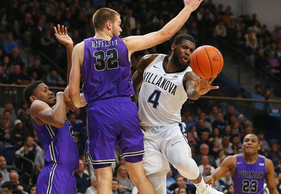 VILLANOVA, PA - NOVEMBER 17: Eric Paschall #4 of the Villanova Wildcats makes a pass as Noah Gurley #4 and Matt Rafferty #32 defend during the second half of a game at Finneran Pavilion on November 17, 2018 in Villanova, Pennsylvania. Furman defeated Villanova 76-68. (Photo by Rich Schultz/Getty Images)