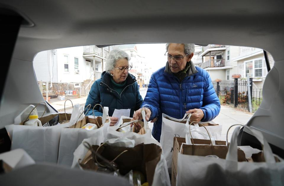 Sharryn Ross and Jon Truslow took a food order from the back of the family vehicle. The couple has been volunteering at Community Servings for more than two decades, delivering meals to people in need in the Boston area.