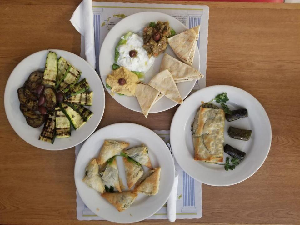 An array of appetizers, including tzatziki, hummus, melitzanosalata, and spanakopita, at Peter's Greek Kitchen in Waltham.