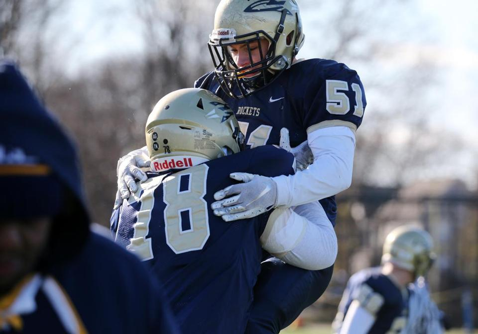 Needham's Jake Schneider (78) and Mason Colwell (51) celebrate a turnover during the 131st football game between Wellesley and Needham at Needham High School. Needham won 14-13.