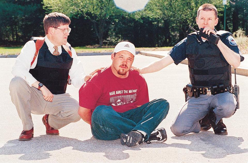 "Concord Police Lt. Paul Gagnon (left) and Sgt. Glenn ""Sam"" Wasp (right) with the the suspect, Todd Bonenfant, in the Monitor parking lot after he walked out of the building and surrendered to Concord Police. Habib photo"