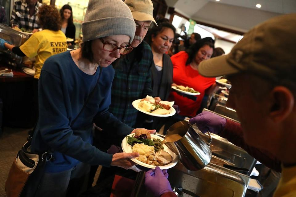Camp Fire evacuees wait in line to receive a free Thanksgiving meal at Sierra Nevada Brewery in Chico, Calif.