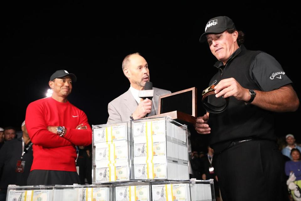 LAS VEGAS, NV - NOVEMBER 23: Phil Mickelson celebrates with the winnings after defeating Tiger Woods as Ernie Johnson looks on during The Match: Tiger vs Phil at Shadow Creek Golf Course on November 23, 2018 in Las Vegas, Nevada. (Photo by Christian Petersen/Getty Images for The Match)