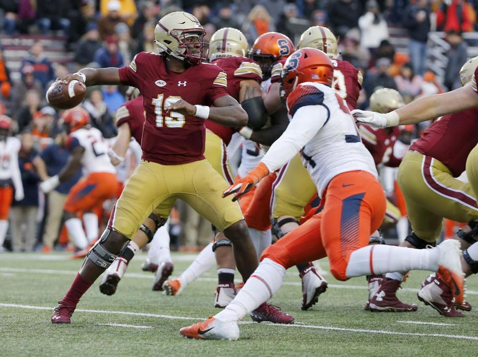 BC quarterback Anthony Brown (13) looks to pass under pressure from a Syracuse defender.