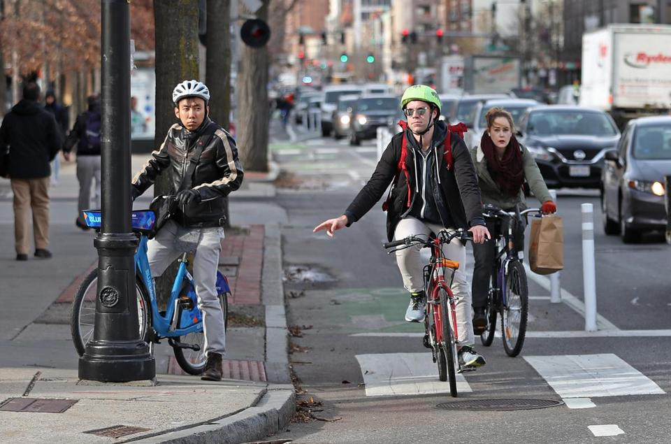 Cyclists use the new bike lane that separates bikes from moving traffic.