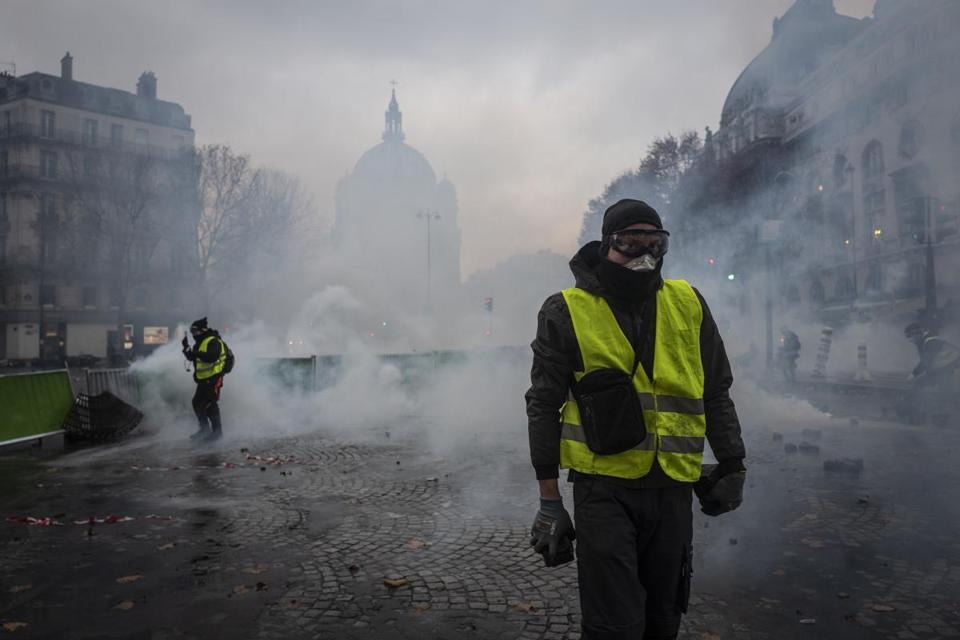 PARIS, FRANCE - DECEMBER 01: Teargas surrounds protesters as they clash with riot police during a 'Yellow Vest' demonstration near the Arc de Triomphe on December 1, 2018 in Paris, France. The third 'Yellow Vest' (gilets jaunes) rally in Paris over increased fuel taxes and leadership in the government today caused over 150 arrests in the city with reports of injuries to protesters and security forces from violence that irrupted from the clashes. (Photo by Veronique de Viguerie/Getty Images)