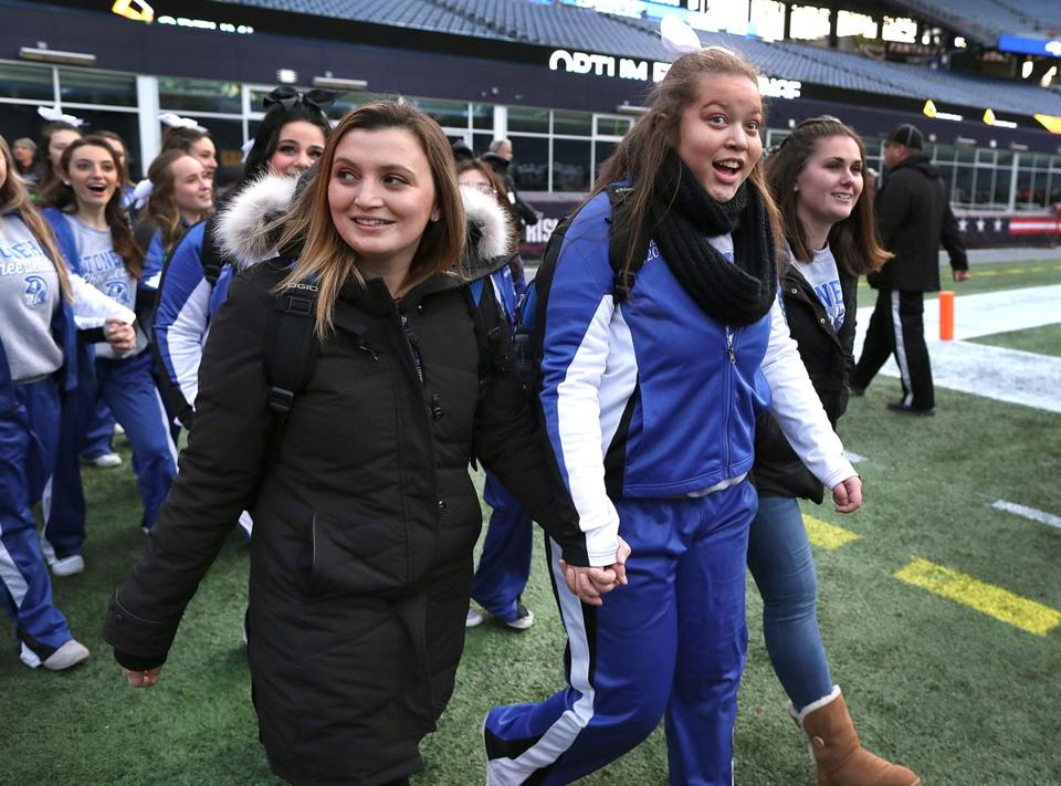 Stoneham cheerleader Autumn Bardell (center) walks with Jackie D'Amato (left) as they enter Gillette Stadium before their team played Old Rochester in the Division 6 Super Bowl.