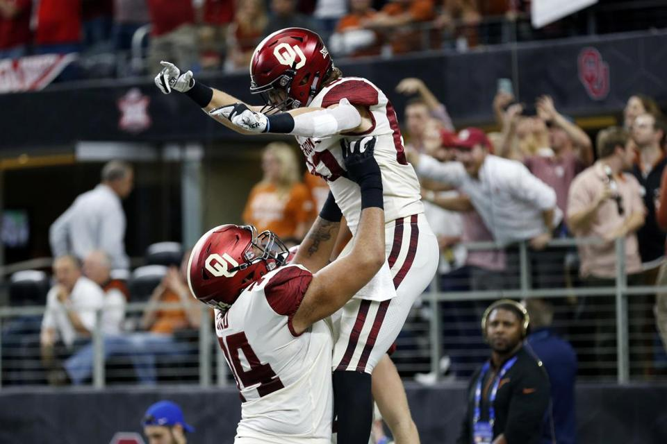 Oklahoma Sooners tight end Grant Calcaterra (right) celebrates a touchdown with offensive tackle Cody Ford (left) during the first half of the NCAA Big 12 Conference football championship against the Texas Longhorns, Saturday, Dec. 1, 2018, in Arlington, Texas. Oklahoma defeated Texas 39-27. (AP Photo/Roger Steinman)