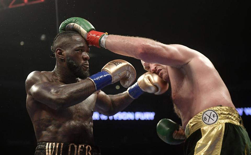 Deontay Wilder, left, and Tyson Fury, of England, trade punches during a WBC heavyweight championship boxing match, Saturday, Dec. 1, 2018, in Los Angeles. (AP Photo/Mark J. Terrill)