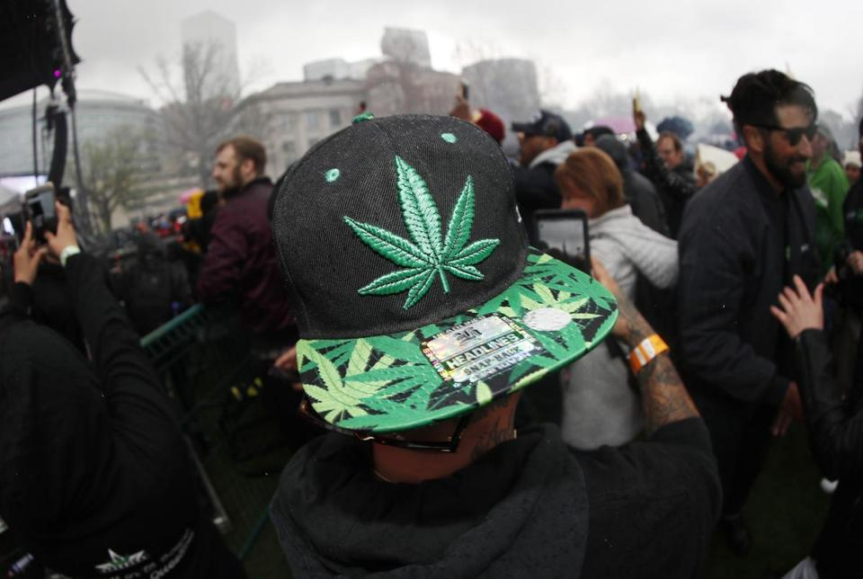 FILE - In this April 20, 2018 file photo, an attendee celebrates at 4:20 p.m. by lighting up marijuana during the Mile High 420 Festival in Denver. Officials in Colorado's largest city say they are working on a plan to clear thousands of marijuana convictions prosecuted before its use became legal in the state. A spokeswoman for Denver's mayor said city officials are working with the local district attorney's office to determine the right approach. (AP Photo/David Zalubowski, File)