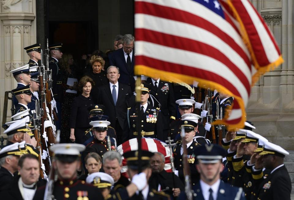 Former President George W. Bush and his wife Laura Bush, center left, join their family as they follow the casket of former President George H.W. Bush as it is carried out after a State Funeral at the National Cathedral in Washington, Wednesday, Dec. 5, 2018. (AP Photo/Susan Walsh)