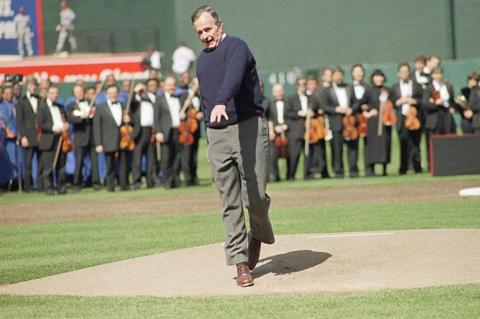 President George H.W. Bush reacts after throwing a one-hopper, the ceremonial first pitch, to Baltimore Orioles catcher Chris Hoiles to open Oriole Park at Camden Yards in Baltimore on Monday, April 6, 1992. The Orioles opened the new stadium playing the Cleveland Indians. Last year at the Texas Rangers home opener, the president also threw the ceremonial pitch on one hop. (AP Photo/J. Scott Applewhite)