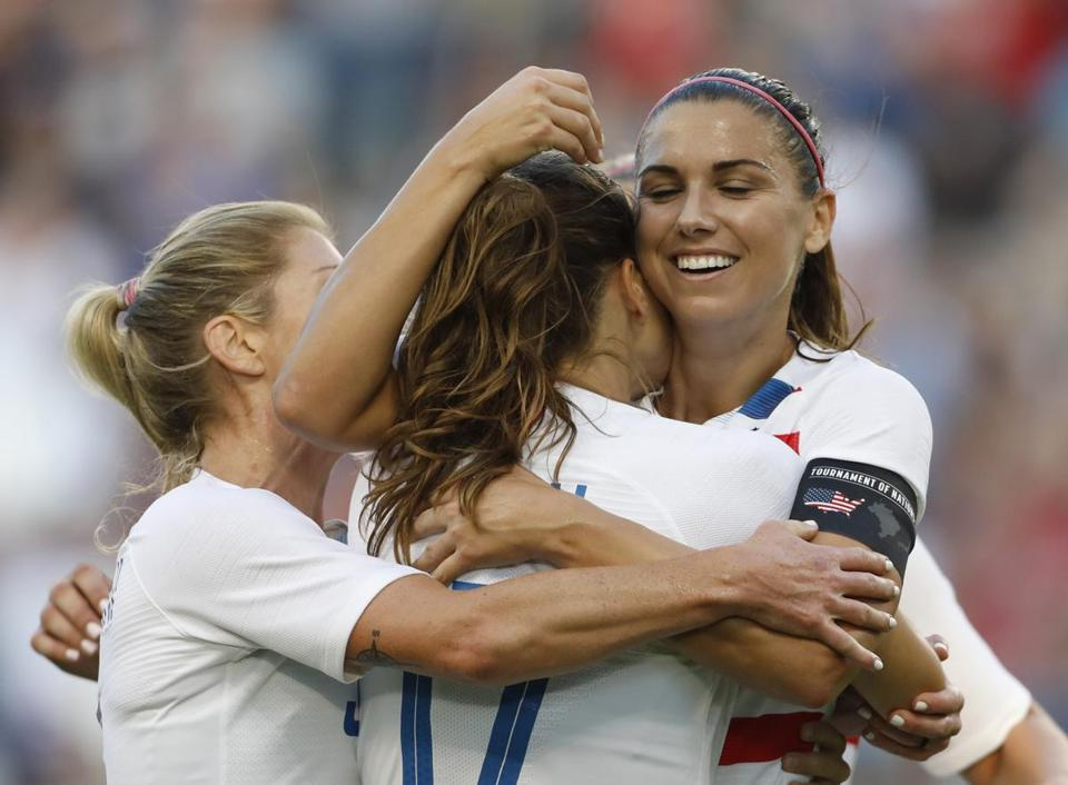 FILE - In this July 26, 2018, file photo, U.S. forward Alex Morgan, right, celebrates her hat trick with defender Tobin Heath (17) and other teammates during the second half of a Tournament of Nations soccer match against Japan, in Kansas City, Kan. Morgan, who had 18 goals in 19 games this year to lead the national team, has been named U.S. Soccer's Player of the Year. (AP Photo/Colin E. Braley, File)