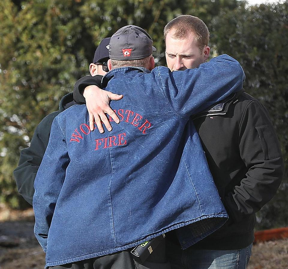 Worcester fire Lieutenant Steven Oberg (left) embraces another member of the force at the scene.