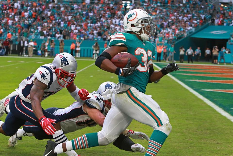 Miami Gardens, FL 12-9-18: The Dolphins Kenyan Drake is about to get into the end zone as the Patriots J.C. Jackson (27) and Rob Gronkowski (87) dive, but can't stop him as he scores the game winning touchdown on the last play of the game. Miami stunned New England 34-33. The New England Patriots visited the Miami Dolphins in a regular season NFL football game at Hard Rock Stadium. (Jim Davis/Globe Staff)