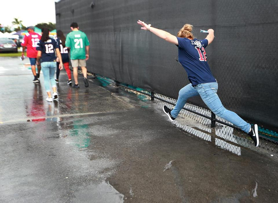 After a heavy rain storrm came through the area before the game, a Patriots fan hurdled a puddle outside Hard Rock Stadium.