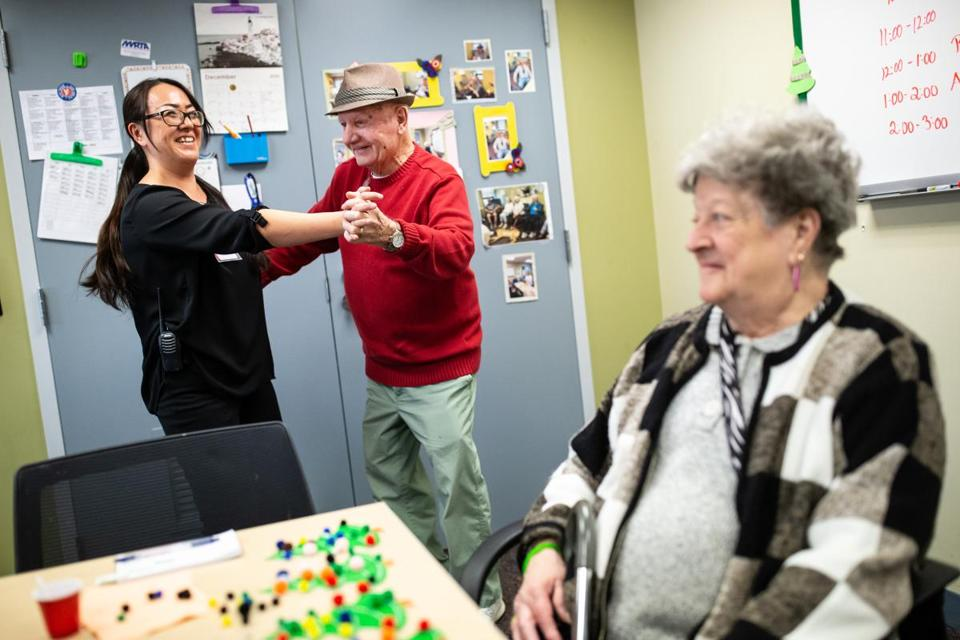 12/11/2018 AMESBURY, MA L-R Activities leader Ayako Tarbell (cq) dances with Ron St. Jean (cq) 82, while Sandra Kowalski (cq) 77, makes crafts during Greenleaf Supportive Day at the Amesbury Council on Aging. (Aram Boghosian for The Boston Globe)