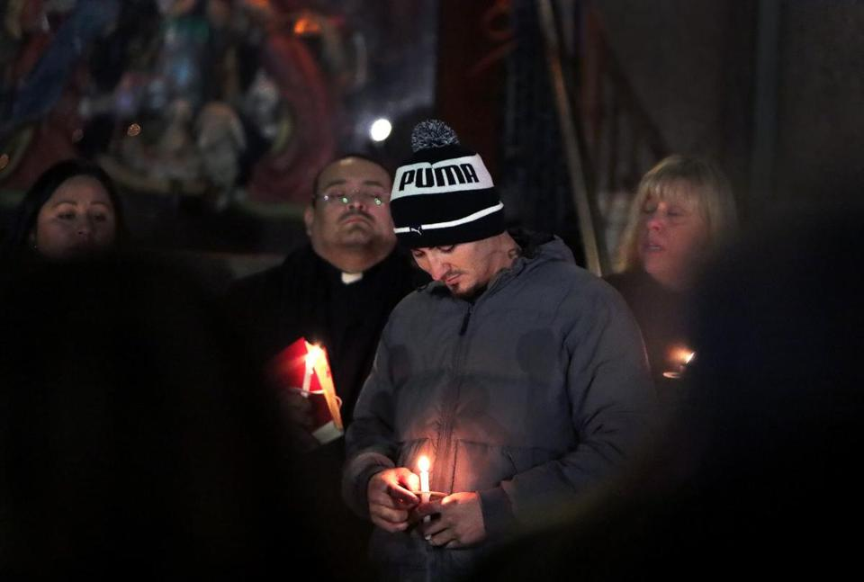 Edgar Mejia, lit candle in hand, at Thursday's vigil for his daughters, who were killed Dec. 9.