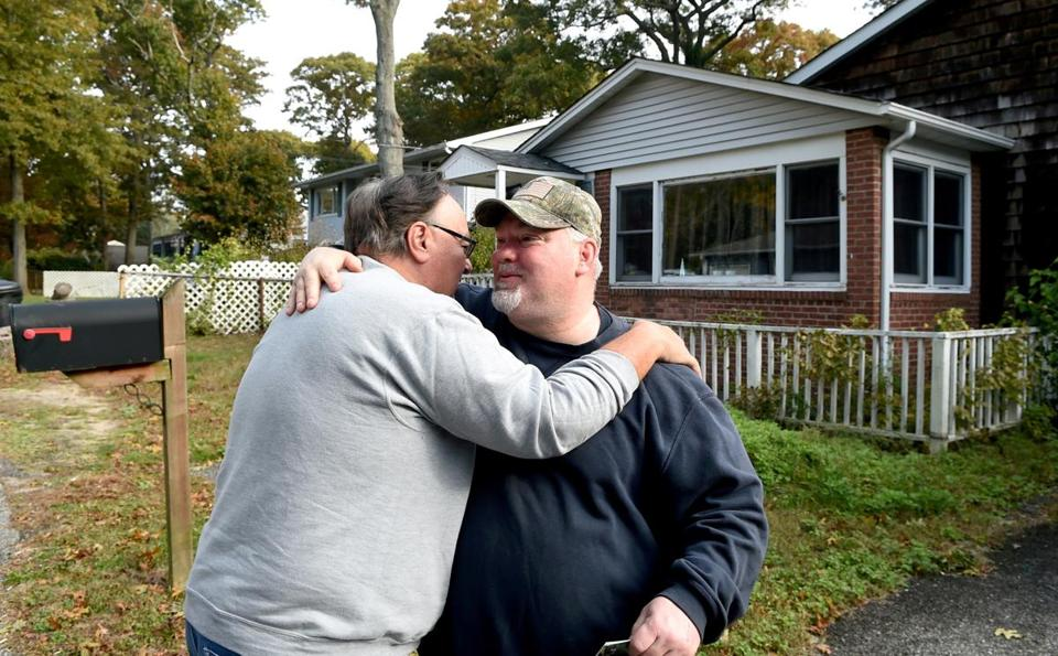 Tony Mraz (left) hugged friend Mike Carroll in front of Carroll's home in Lake Grove, N.Y., where the remains were discovered.