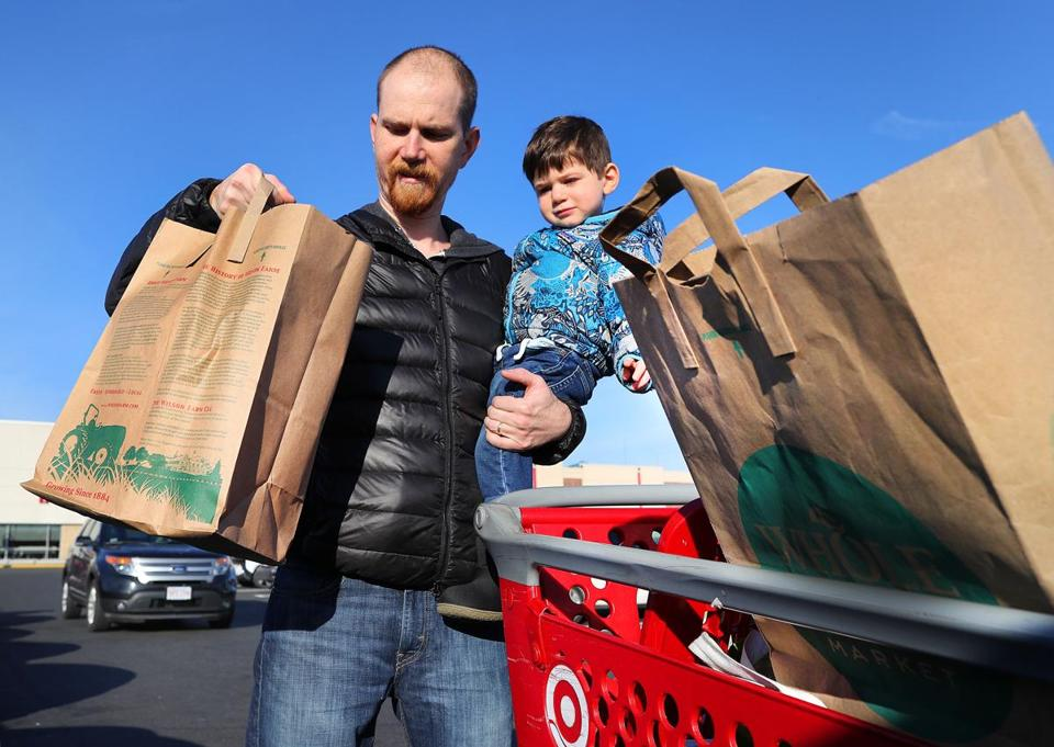 Dorchester 12/14/18 Boston's ban on plastic bags began on Friday, as customers to the Target store in the South Bay Mall walked out with paper bags. John Lynch from Boston holds his son Owen, 2 as he puts his reused paper bags into his trunk after shopping at Target. Photo by John Tlumacki/Globe Staff(metro)