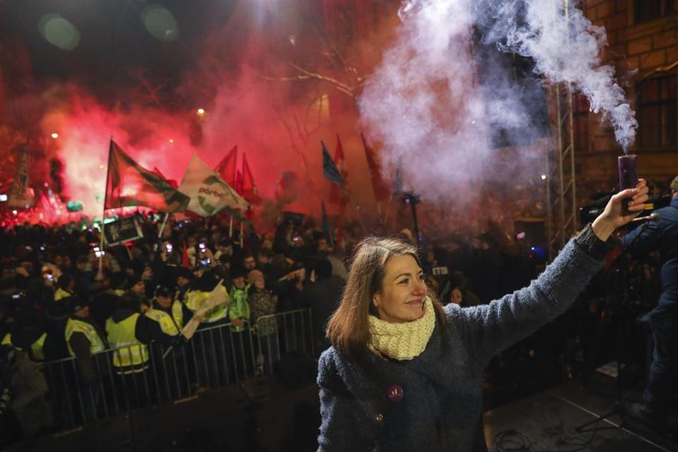 Anna Donath, vice chairwoman of the Momentum party, held a smoke grenade during a protest in Budapest on Sunday.