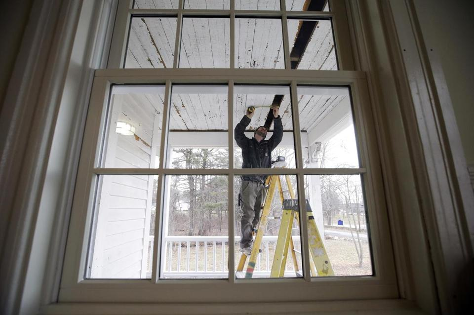 In this Thursday, Dec. 13, 2018 photo, carpenter Jeremy Parker works on a porch at the conclusion of a restoration of the home where Sarah Clayes lived, in Framingham, Mass., after leaving Salem, Mass., following the 1692 witch trials. Clayes was jailed during the witch trials but was freed in 1693 when the hysteria died down. (AP Photo/Steven Senne)