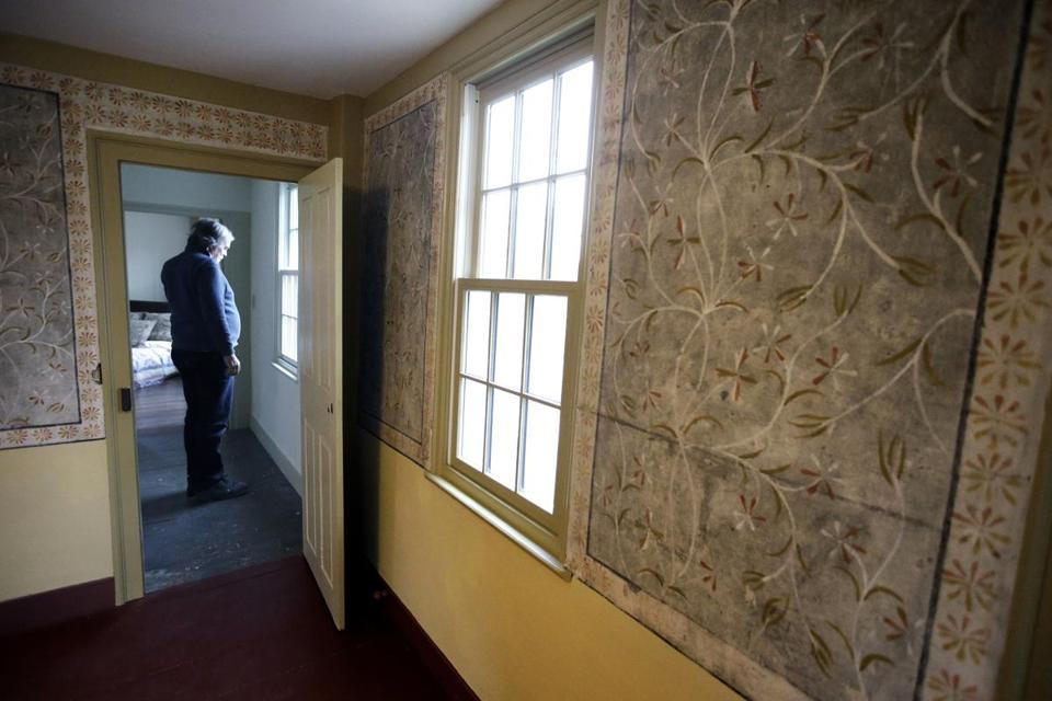 In this Thursday, Dec. 13, 2018 photo builder Ned Murphy stands near a window outside a room that features historic paint-on-plaster murals at the home where Sarah Clayes lived, in Framingham, Mass., after leaving Salem, Mass., following the 1692 witch trials. The once-run-down home that stands where Clayes, a woman accused of witchcraft during the 1692 Salem witch trials settled, is on the market after an extensive renovation project. (AP Photo/Steven Senne)