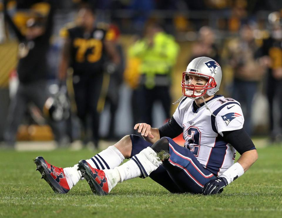 Tom Brady sits on the turf after his last pass of the game fell incomplete in the end zone.