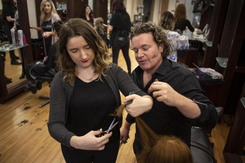 Melanie Warner left works on her hair cutting techniques with educator/stylist Alex Paulsen at Salon Herdis in Northampton, Mass. The owner of Salon Herdis is pre-emptively raising the wages of entry-level employees.