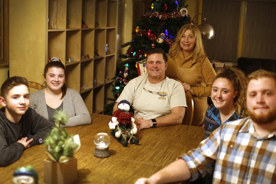 The Winschel family in their Peabody home (from left): Kevin, Sophia, parents Daniel and Ellen,  Marlana, and Justin. Daniel Winschel has spent nearly four years away from his family over 32 years of service.