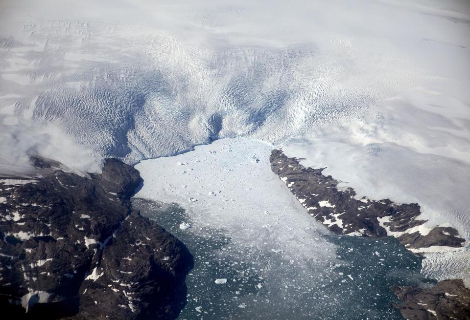 A glacier calves icebergs into a fjord off the Greenland ice sheet in southeastern Greenland, Thursday, Aug. 3, 2017. The Greenland ice sheet, the second largest body of ice in the world which covers roughly 80 percent of the country, has been melting and its glaciers retreating at an accelerated pace in recent years due to warmer temperatures. (AP Photo/David Goldman)
