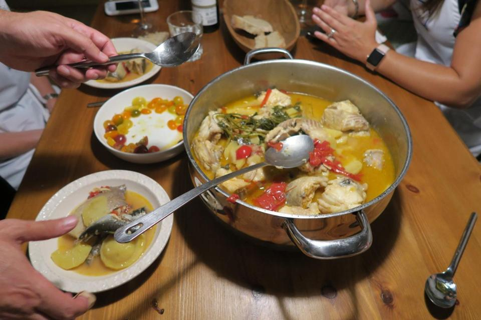 Top to bottom: Caldeirada, a traditional fish stew, is served; Ricardo Dias Felner prepares Portuguese dishes in his home; ingredients of the fish stew are layered in a bowl; garlicky baby clams were part of the meal; a pre-meal snack of local cheeses and chorizo along with Sagres beer.