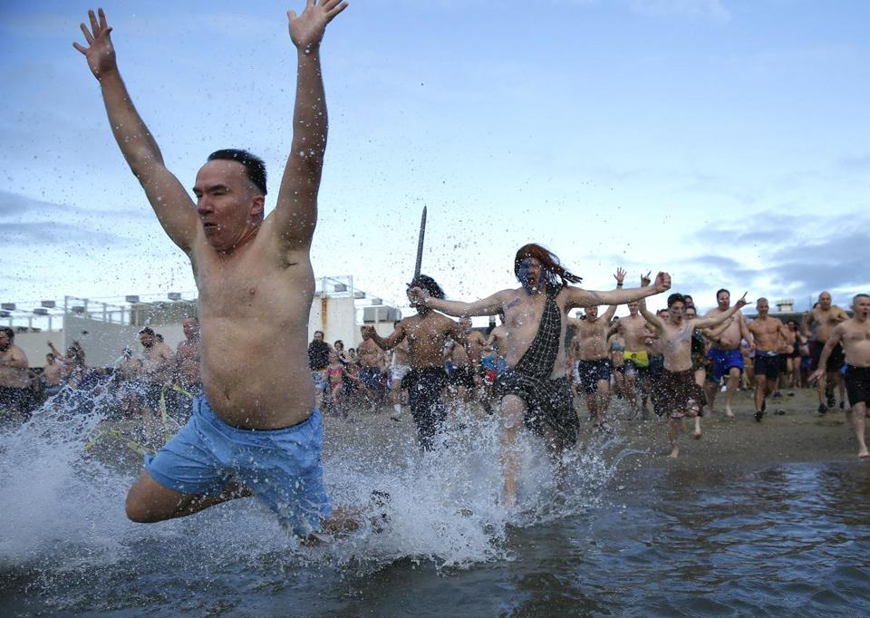 People ran into the water during the L Street Brownies' annual New Year polar plunge.