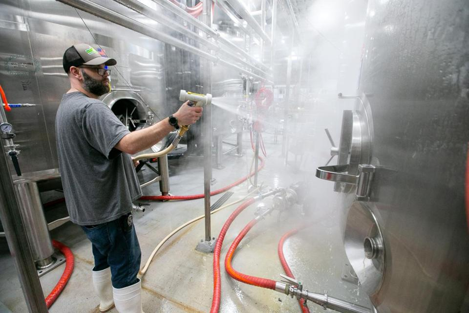 Robin DeLand, cellerman with Tree House Brewing Company, hosed down the outside of a bright tank while cleaning it at the brewery in Charlton.