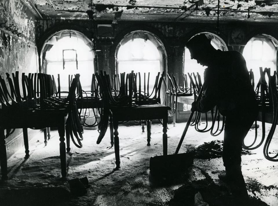 Boston, MA - 2/7/1968: A person cleans the inside of the burned dining room of Durgin-Park after a fire in Boston, Feb. 7, 1968. (Joyce Dopkeen/Globe Staff) --- BGPA Reference: 170926_ON_002