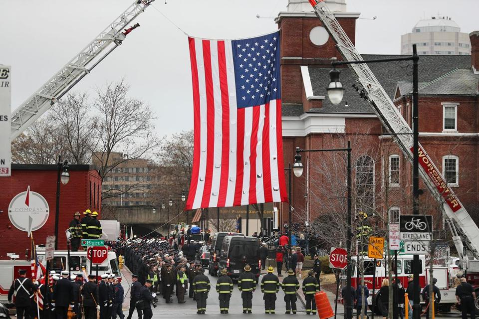 Worcester 12/15/18 A huge American flag hangs near St. John's Catholic Church from two Worcester Fire Dept. trucks or Worcester firefighter Christopher Roy who died battling a fire last weekend. The funeral was held at St. John's Catholic Church(rear right). Photo by John Tlumacki/Globe Staff(metro)