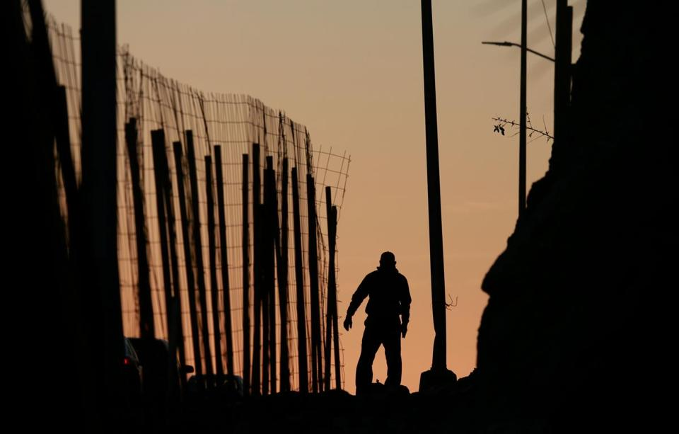 TIJUANA, MEXICO - JANUARY 7: A man walks along a road next to the U.S.-Mexico border wall on January 7, 2019 in Tijuana, Mexico. President Donald Trump, who is planning on visiting the border on Thursday, is considering declaring a national emergency if Democrats do not approve of 5.7 billion dollars in funding to build a wall. (Photo by Sandy Huffaker/Getty Images)